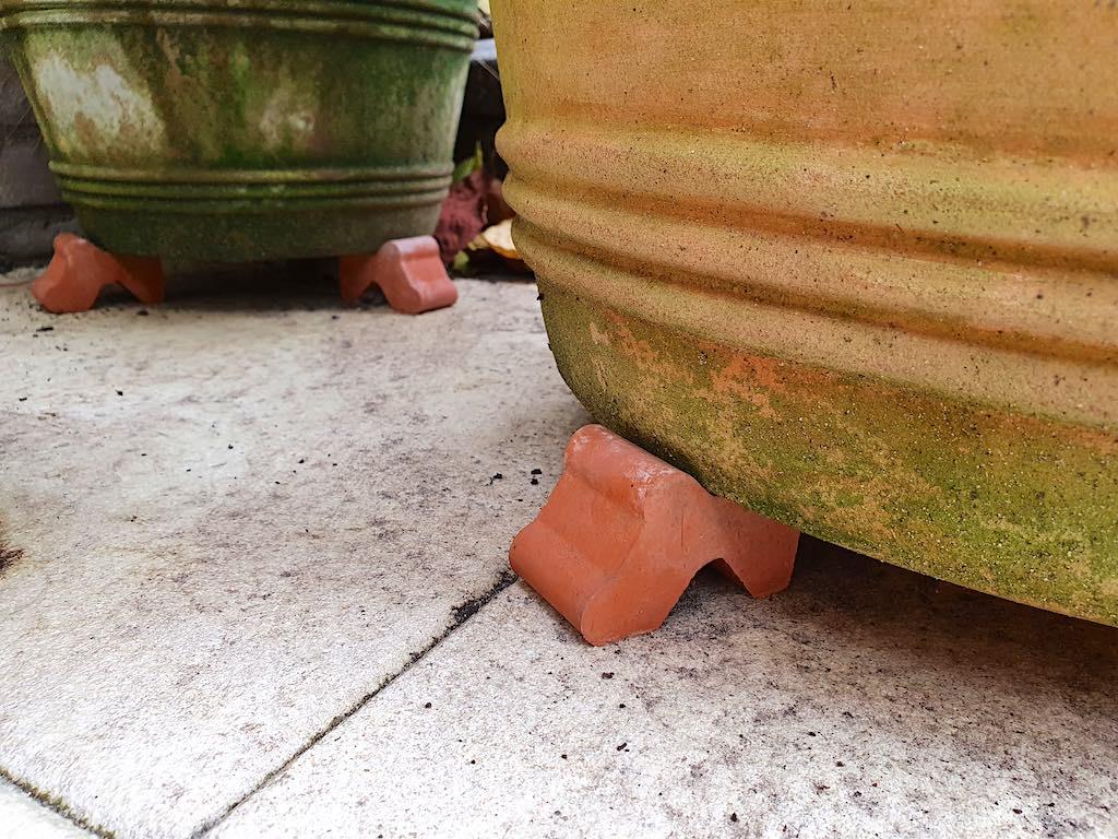 Plaats Terracotta potten op voetjes en reinig lege potten, zodat ze klaar zijn voor hergebruik